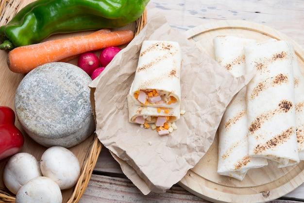 Frühstücks-burrito mit eiern, cheddar, microgreens und gerösteten pilzen