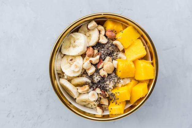 Frühstücks-haferbrei mit frischen früchten, chiasamen und haselnüssen.
