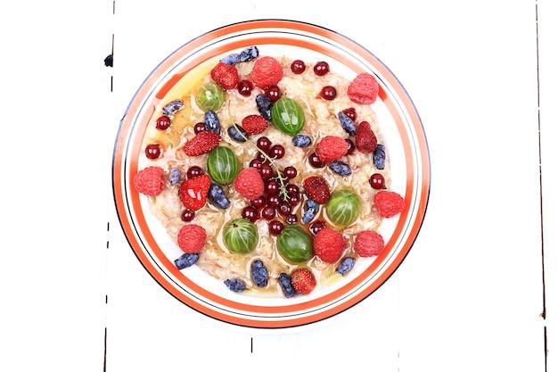 Frühstücks-haferflocken mit beeren und honig auf weißem holzhintergrund im flachen stil draufsicht overhead-summe...