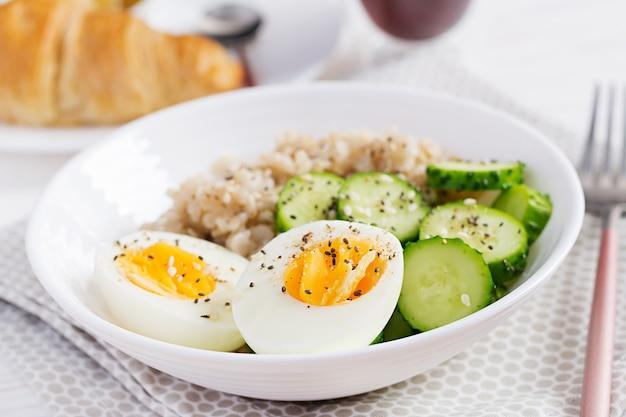 Frühstücks-haferflockenbrei mit gekochtem ei, gurke und sesamsamen. gesundes ausgewogenes essen.