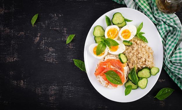 Frühstücks-haferflockenbrei mit gekochten eiern, lachssandwich und gurkensalat. gesundes essen. mittagessen. ansicht von oben, flach