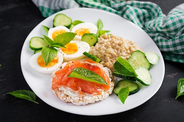Frühstücks-haferflockenbrei mit gekochten eiern, lachssandwich und gurkensalat. gesundes essen. mittagessen.