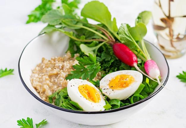 Frühstücks-haferflockenbrei mit gekochten eiern, rettich und grünen kräutern. gesundes ausgewogenes essen.