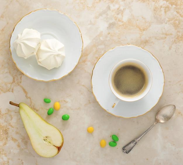 Frühstücks-marshmallows auf der untertasse, eine halbe birne und eine tasse kaffee