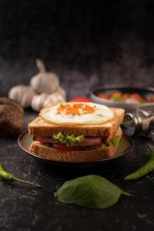 Frühstücks-sandwich mit brot, spiegelei, schinken und salat.
