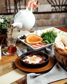 Frühstücksaufbau mit ei mit würstchen pfannkuchen kräuter käse gemüse und tee