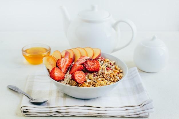 Frühstücksbrei haferflocken mit müsli-müsli-erdbeeren-pfirsich-honig in einem weißen teller auf dem hintergrund einer weißen teekanne und schalen mit honig auf einem weißen teller