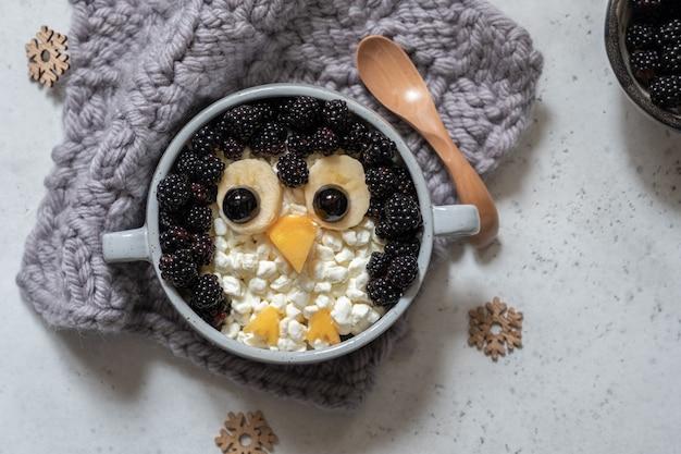 Frühstücksbrei mit pinguinform aus beeren
