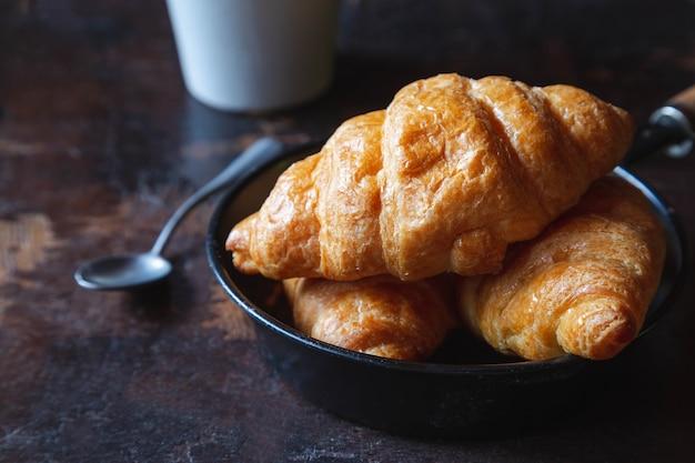 Frühstücksbrot, croissants und frische milch auf dem holztisch.