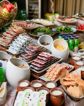 Frühstücksbuffet mit buttermarmeladen, joghurt und keksen