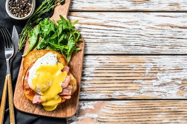 Frühstücksburger mit speck, ei benedict, sauce hollandaise auf briochebrötchen. mit rucola-salat garnieren. weißer hintergrund.