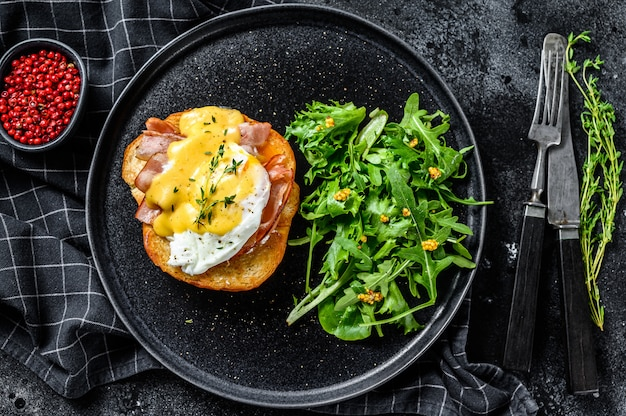 Frühstücksburger mit speck, ei benedict, sauce hollandaise auf briochebrötchen. schwarzer hintergrund. draufsicht