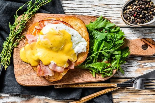 Frühstücksburger mit speck, ei benedict, sauce hollandaise auf briochebrötchen