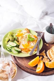 Frühstückseier auf einem weißen teller mit halber avocado, gurken auf einem holzteller auf dem bett