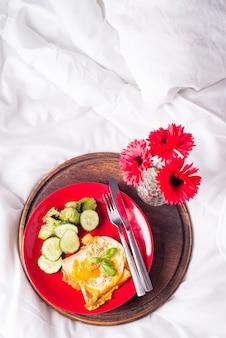 Frühstückseier auf einem weißen teller mit halber avocado, gurken auf einem roten teller auf dem bett mit blumen