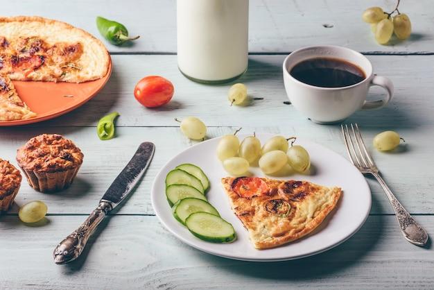 Frühstücksfrittata mit chorizo-tomaten und chilischoten auf teller mit tasse kaffee