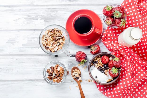 Frühstücksgranola, erdbeere und ein tasse kaffee