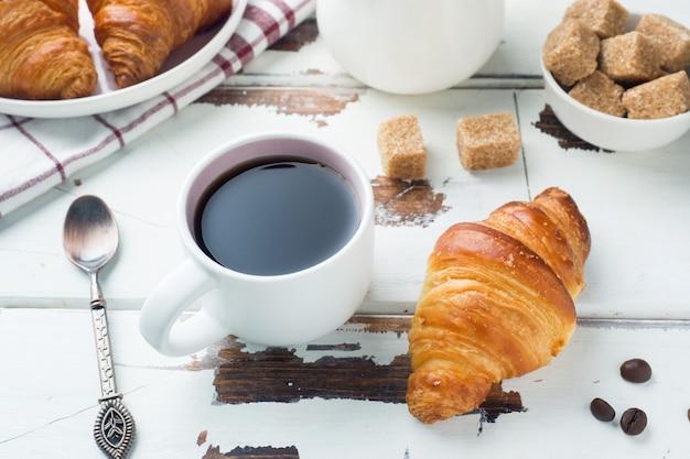 Frühstückshörnchen auf einer platte und einem tasse kaffee, holztisch.