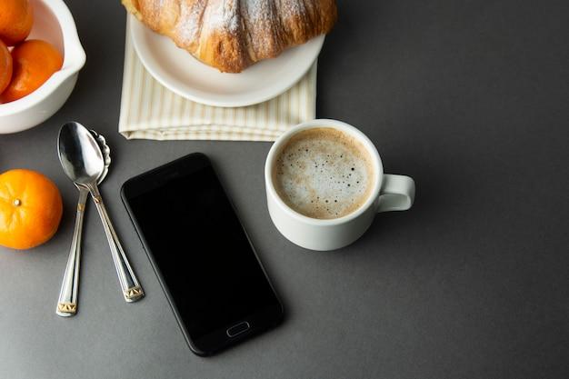 Frühstückskaffee mit croissant, französischen zitrusfrüchten, gebäck, einer tasse kaffee oder latte. koffein wird angepriesen.