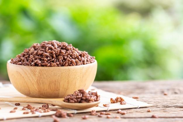 Frühstückskost aus getreide, puffreis mit kakao in der schüssel auf holztisch mit grünem unschärfebereich
