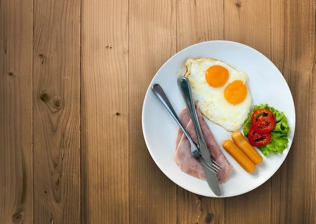 Frühstücksmenü mit ei, schinken, wursttomate und grünem gemüse