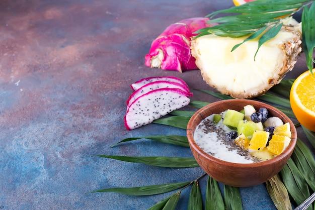 Frühstücksmoothieschüssel überstiegen mit pitaya, ananas, chia samen und beeren mit palmblatt auf steinhintergrund, draufsicht