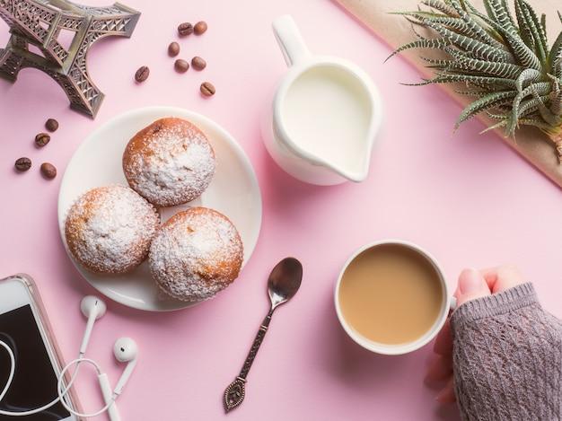 Frühstücksmuffinkaffee-milchkrug auf einem rosa hintergrund. draufsicht flach legen.