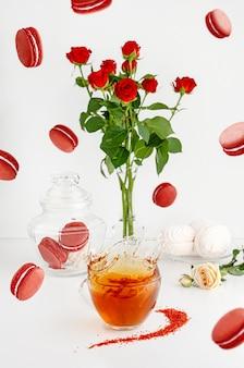 Frühstücksnachtische auf weißem hintergrund mit makronen, blumenstrauß von roten rosen und dem spritzen des tees.