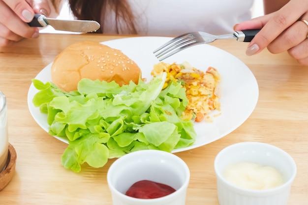 Frühstücksomelett, brot, hamburger und gemüse auf einem weißen teller mit messer und gabel essen
