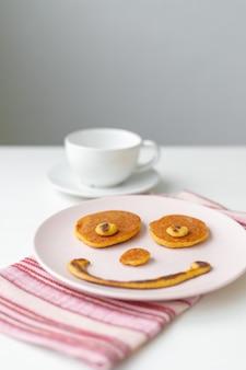 Frühstückspfannkuchen in form eines lächelns auf einem rosa teller