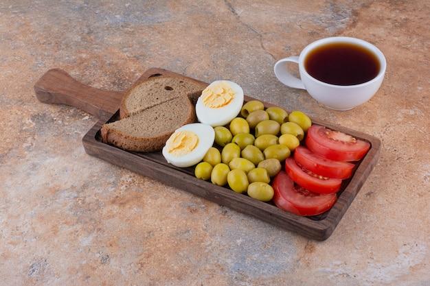 Frühstücksplatte mit brot und einer tasse tee