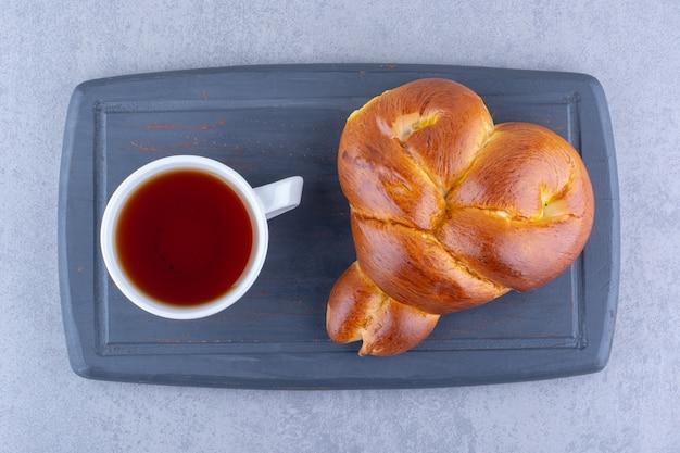 Frühstücksportion tee und süßes brötchen auf einem brett auf marmoroberfläche