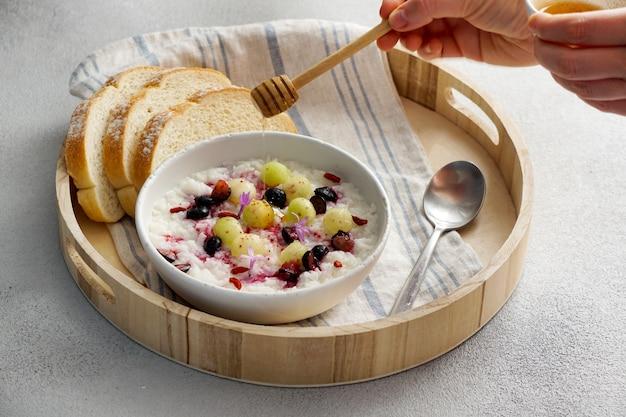 Frühstücksreisbrei mit honig und melone, beeren