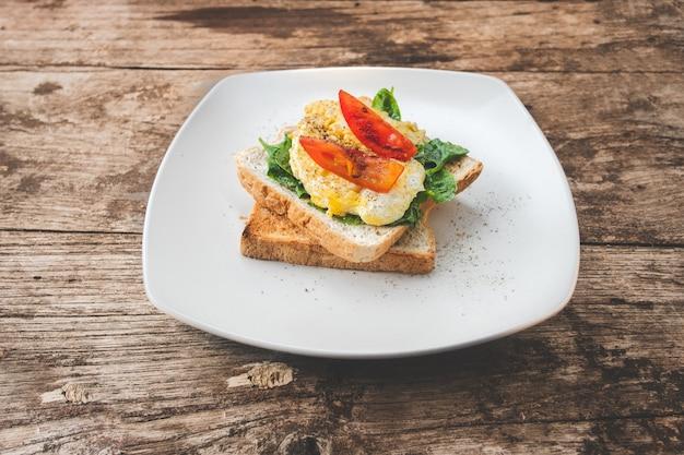 Frühstückssandwich mit ei, brunnenkresse und tomate auf dem holztisch, gesundes lebensmittel