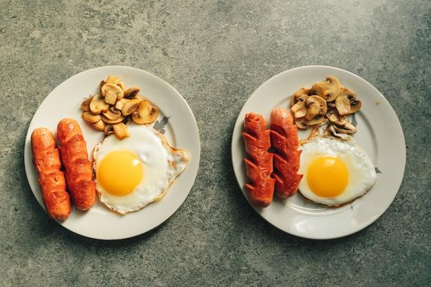 Frühstückssatz von würstchen spiegeleiern und pilzen auf der küchentheke im warmen morgenlicht.