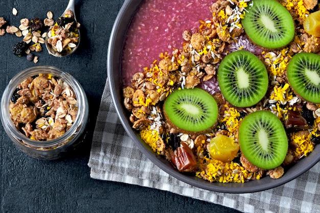 Frühstücksschale mit acai smoothie, haferflocken, müsli und obst.