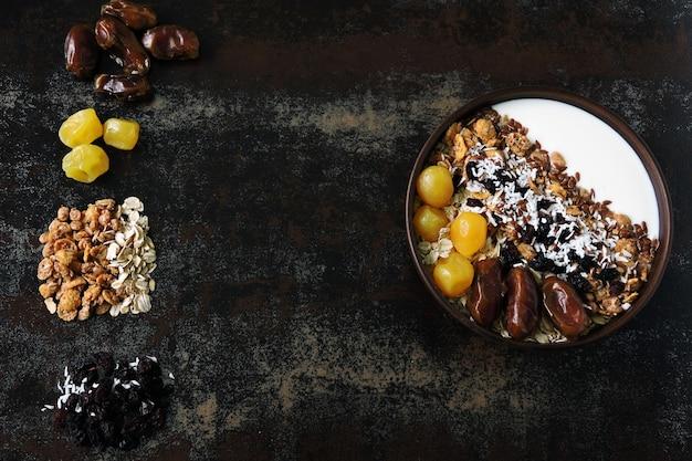Frühstücksschale mit griechischem joghurt, haferflocken, müsli und getrockneten früchten.