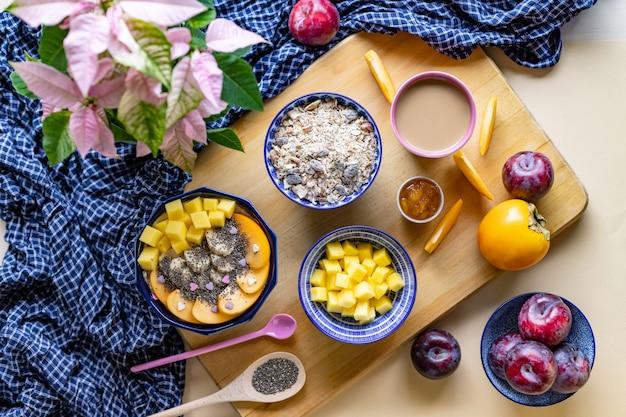 Frühstücksschale mit hafer, joghurt, mango, persimone und chia, draufsicht
