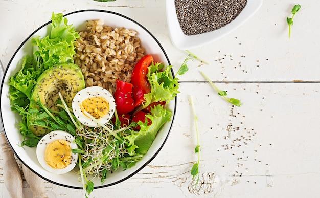 Frühstücksschüssel mit haferflocken, paprika, avocado, salat, microgreens und gekochtem ei.