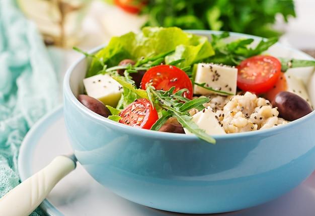 Frühstücksschüssel mit haferflocken, tomaten, käse, salat und oliven