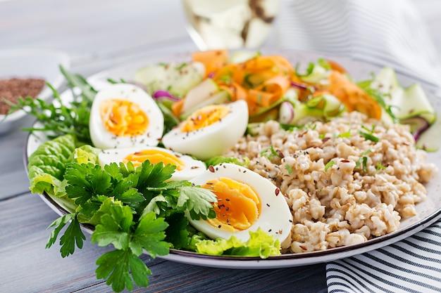 Frühstücksschüssel mit haferflocken, zucchini, salat, karotte und gekochtem ei