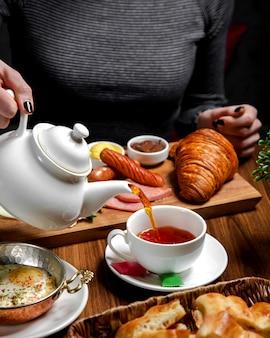 Frühstücksset auf dem tisch mit schwarzem tee