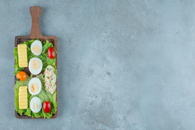 Frühstücksset auf einem holztablett mit gemüse, gekochten eiern, butter und einer salatportion auf marmorhintergrund. hochwertiges foto