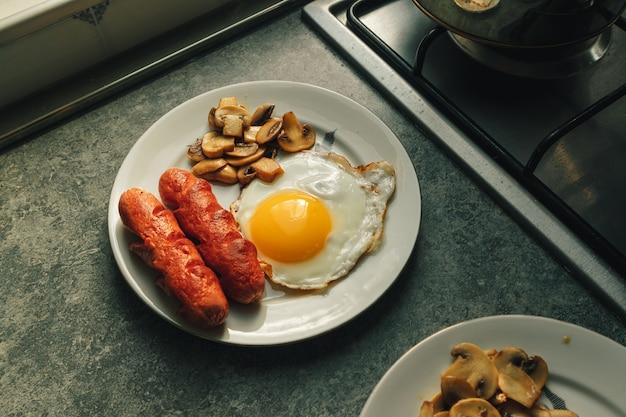 Frühstücksset aus spiegelei und würstchen mit pilzen in der küche.