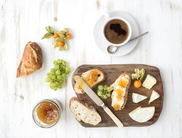 Frühstücksset. briekäse- und feigenmarmeladensandwiches mit frischen trauben, gemahlenen kirschen. tasse kaffee. ansicht von oben