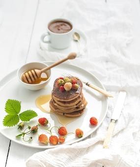 Frühstücksset. buchweizenpfannkuchen mit frischen gartenerdbeeren, honig und tasse kaffee über weißem holztisch