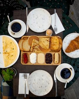 Frühstücksset mit crepes pfannkuchen, toast, croissant, ei, geschnittenen erdbeeren, bananen und kaffee