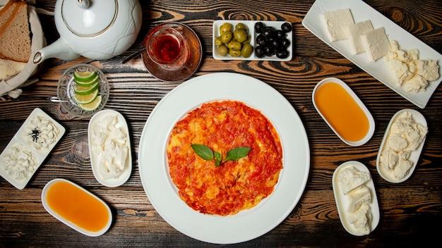 Frühstücksset mit käse, honig, tee und einer warmen mahlzeit