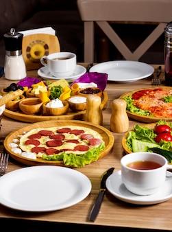 Frühstücksset mit rührei mit würstchen, frischem salatkäse und einer tasse tee