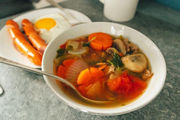 Frühstücksset mit spiegeleiwürsten und gemüsesuppe auf dem tisch serviert.